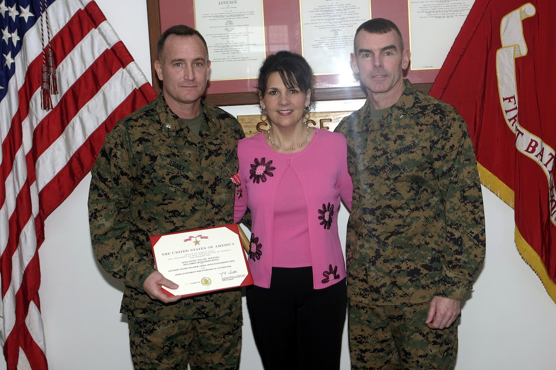 MARINE CORPS BASE CAMP LEJEUNE, N.C. - Lieutenant Colonel William Jurney, 1st Battalion, 6th Marine Regiment's commander, left, poses for a photo alongside his wife, Sue Ellen, and Brig. Gen. Joseph McMenamin, 2nd Marine Division (rear) commanding general, after being presented his Bronze Star Medal with combat distinguishing device here Jan. 17.  Jurney, a Statesville, N.C. native, was recognized for his courageous leadership during his unit's deployment to Iraq from March through October 2005.