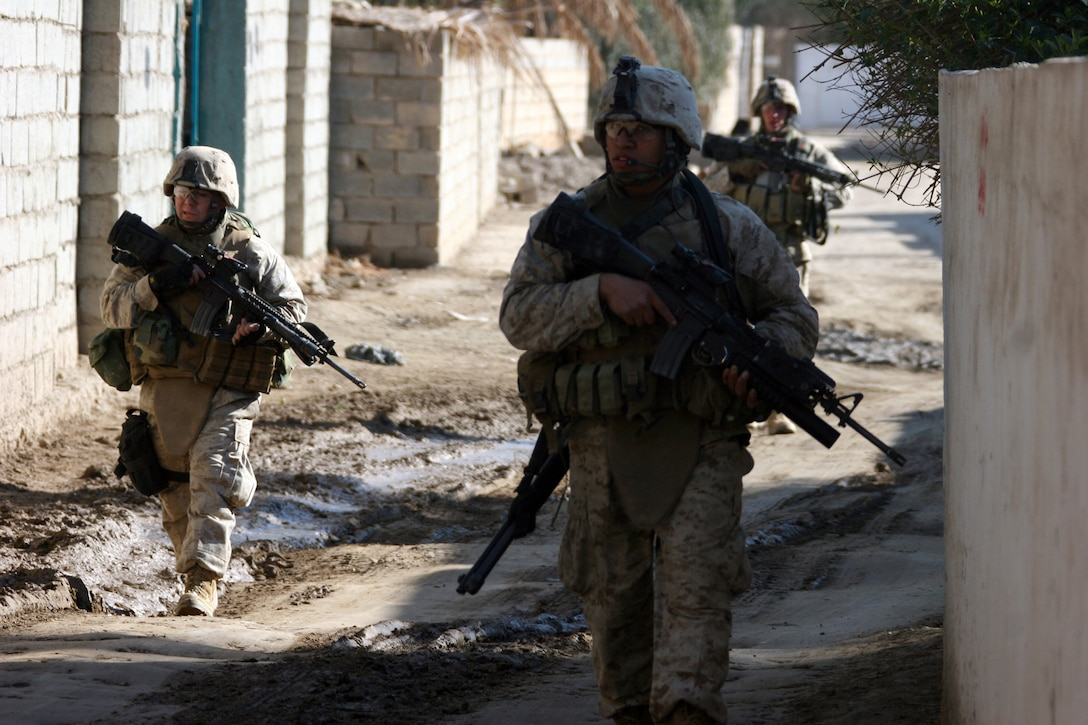 AR RAMADI, IRAQ (January 17, 2006) – Three Marines with Company I, 3rd Battalion, 7th Marine Regiment, patrol behind a unit of the local Iraqi Army during a combined mission Jan. 17. The patrol was part of the training that the Marines are conducting with the IA to prepare them for providing security for their country. Photo by Cpl. Shane Suzuki