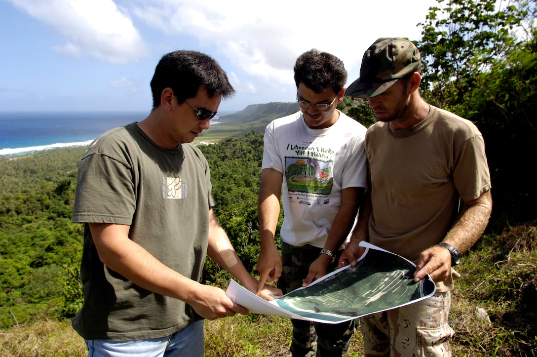 ANDERSEN AIR FORCE BASE, Guam (AFPN) -- Dana Lujan (left), Jeff Quitugua and Chris Jones (right) look over a map of Anderson Air Force Base. Mr. Lujan is the liaison for the Guam Department of Agriculture, which has a partnership with the base to re-introduce the Marianas crow back to the island. Mr. Lujan is the 36th Expedition Air Wing's chief conservation officer. Mr. Quitugua is a wildlife biologist and Mr. Jones is a wildlife technician from the Guam Department of Agriculture. (U.S. Air Force photo by Tech. Sgt. Shane A. Cuomo)