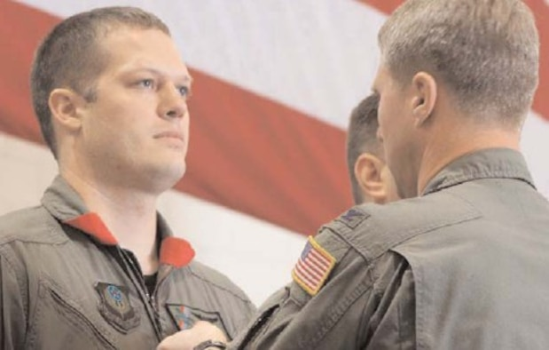 Capt. Matthew Berry, 20th Special Operations Squadron, receives a Distinguished Flying Cross with Valor from Col. Mark Alsid, 16th Operations Group commander, Dec. 16 in Freedom Hanger.