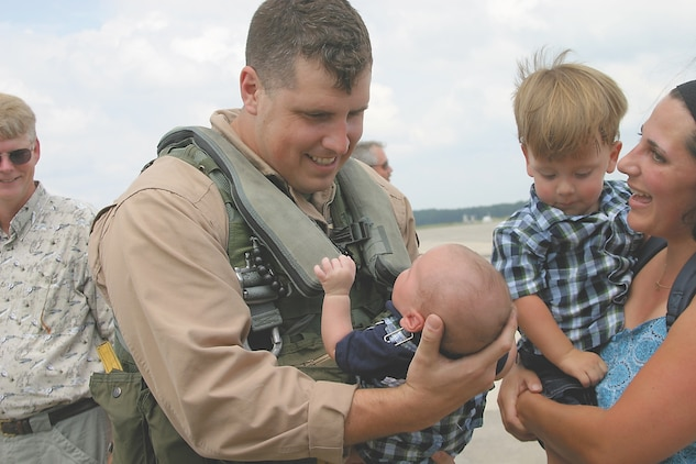 Capt. Robert Johnson, a pilot with Marine All-Weather Fighter Attack Squadron 533 holds his son Owen for the first time.  Owen was born in July while the Hawks were deployed in Al Asad Iraq.  The Hawks recently returned home from a seven-month deployment.