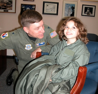 """Eight-year-old Cheyanne Matthews, shares a laugh with Col. James N. Stewart, commander of the 514th Air Mobility Wing, an Air Force Reserve unit at McGuire Air Force Base, N.J., Dec. 3 as part of her visit duirng the """"Hero for the Day"""" program. The program, sponsored by the 732nd Airlift Squadron, is designed to give back to the local community and is open to children who have a terminal disease or debilitating condition. Cheyanne, who suffers from a heart condition called Tetrologyoffallot, has undergone three open heart surgeries since age two. Her latest was performed Dec. 22."""