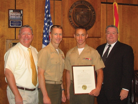 Rep. Russell Jones (left), Arizona House representative for District 24, Col. Ben Hancock, station commanding officer, Cpl. Michael Sandall, Headquarters and Headquarters Squadron Noncommissioned Officer of the Quarter, and Speaker James P. Weiers, Arizona Speaker of the House, pose for a picture after receiving the House Proclamation on May 25 on the Arizona House floor in Phoenix.