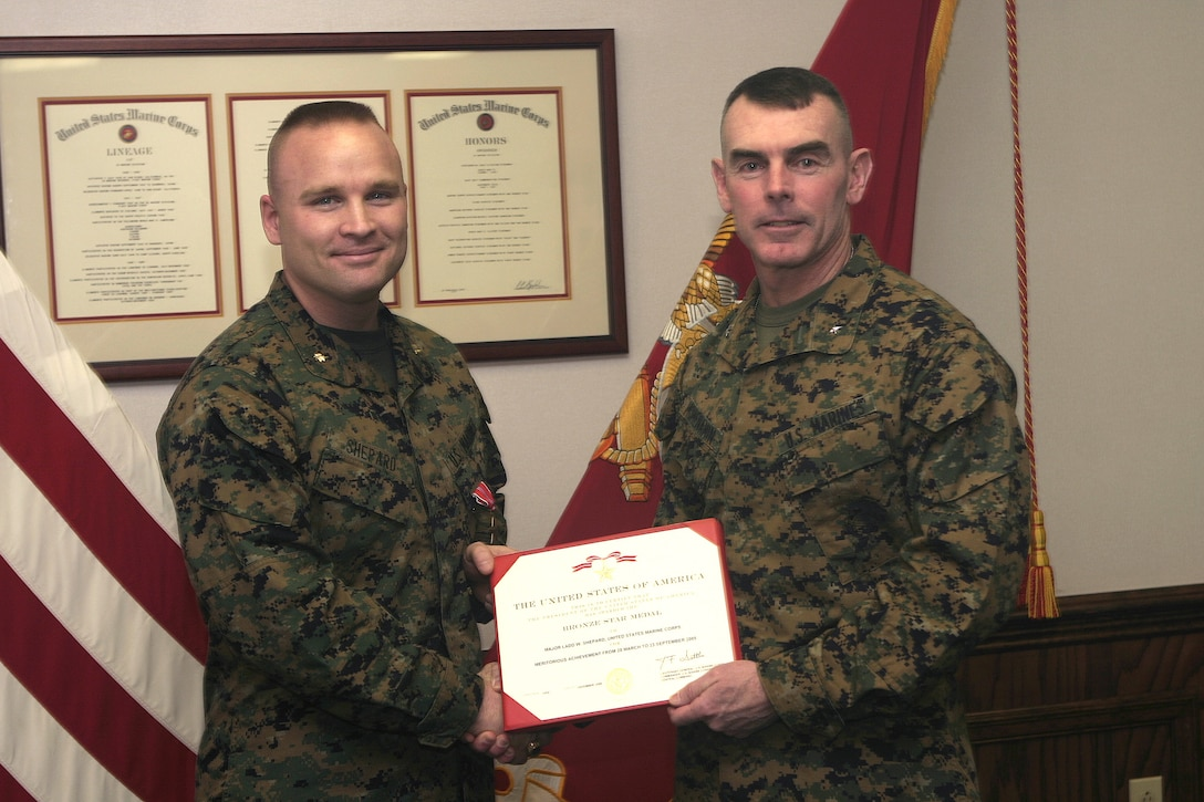 MARINE CORPS BASE CAMP LEJEUNE, N.C. - Major Ladd Shepard, 2nd Light Armored Reconnaissance Battalion's former operations officer, left, is presented his Bronze Star Medal here Jan. 27 by Brig. Gen. Joseph J. McMenamin, 2nd Marine Division's assistant commander.  The 32-year-old Tryon, N.C. native was awarded this prestigious decoration for his and his unit's work conducting counterinsurgency operations in western Iraq from March to September 2005.
