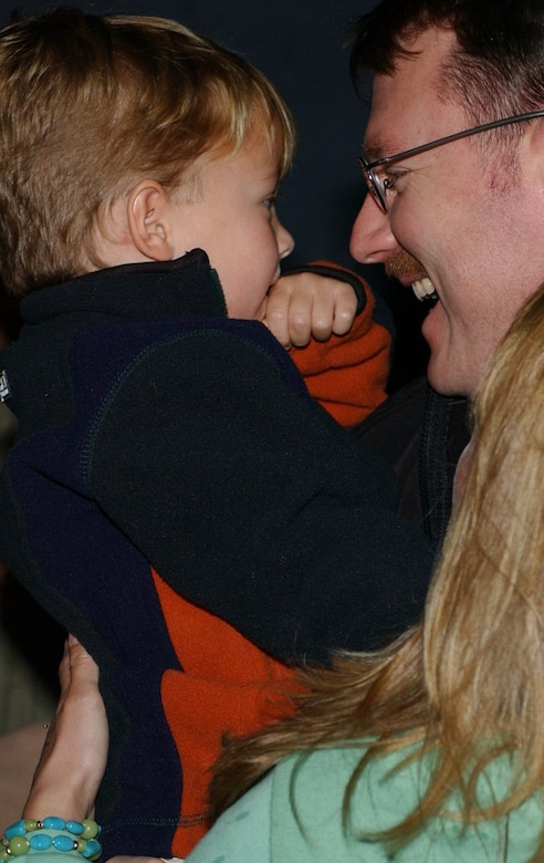 Maj. Michael Pakiz, 15th Special Operations Squadron, hold s his son after returning home from a deployement Jan.17.