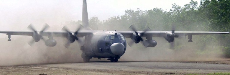 A MC-130 Combat Talon II from the 15th Special Operations Squadron lands on a dirt airfield.