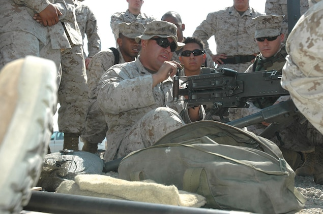 Staff Sgt. David Ramirez, Marine Wing support Squadron 371 production chief, shows Marines the correct way to sit while firing the M2 .50-caliber machine gun at the Yuma Proving Ground's Grave Range on June 29. The Marines have been training at the range for their February development to Iraq.