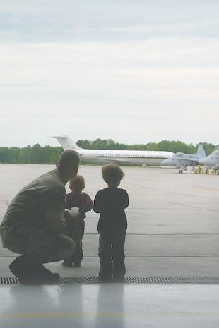 From the shade of the Thunderbolts? hangar, Navy Lt. Mark Flanagan waits with his children, Moxie, right, and Gussie, before boarding a plane bound for Norfolk, Va., April 30. Flanagan is the flight surgeon for Marine Fighter Attack Squadron 251. Both the Thunderbolts and the Sidewinders of Navy Strike Fighter Squadron 86  deployed to the USS Enterprise for a six-month cruise.