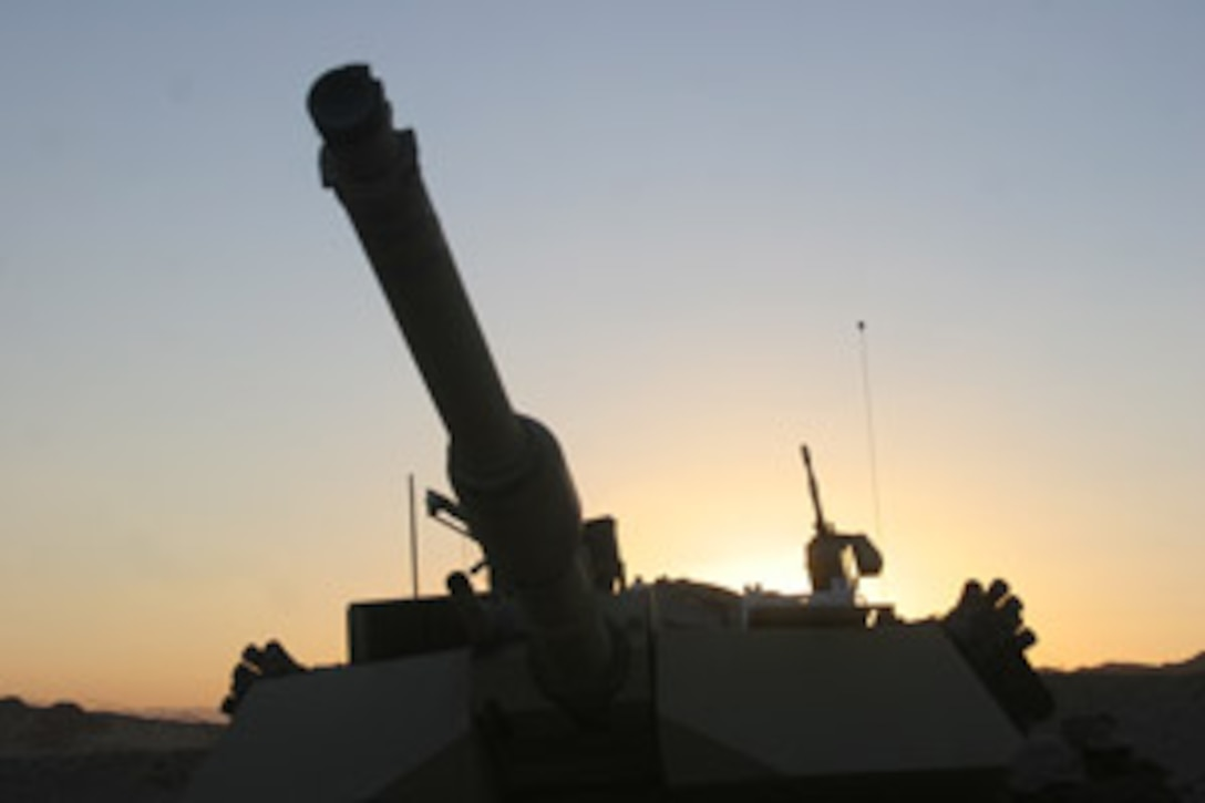 A tank sits in the training area as the sun sets behind it. Marines from 1st Tank Battalion celebrated their 65th birthday Nov.1 at Gray Field.