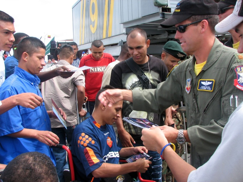 Maj. Jason Koltes hands out mementos to injured Columbian military veterans on Sunday, July 2. Major Koltes is the commander and a pilot for the F-16 Fighting Falcon Viper East aerial demonstration team. The team was in Colombia for the Rio Negro air show. (U.S. Air Force photo/1st Lt. Christina Mundy)
