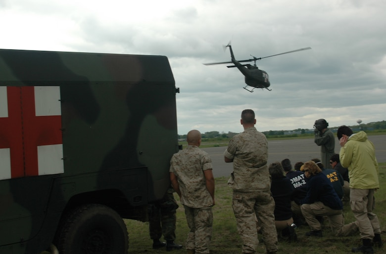 Two Marine ambulance drivers (left) and civilian medical volunteers watch a Rhode Island Army National Guard helicopter lift off from Dogpatch training area. The exercise combined the elements of military and civilian medical technicians in real-world accident scenarios. (U.S. Air Force photo/Master Sgt. Tom Allocco)