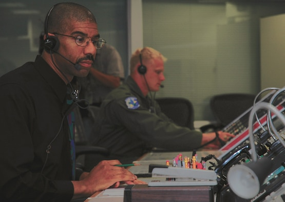 VANDENBERG AFB, Calif. – Wesley Fleming, a mission control supervisor with Indyne Inc., and 1st Lt. David Rodriguez, a range control officer with the 2nd Range Operations Squadron, pull an all-nighter at the Western Range Control Center here to provide tracking for the Space Shuttle Discovery landing. (Photo courtesy 30th Space Wing Public Affairs)