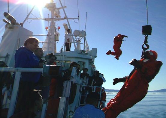 """THULE AB, Greenland – Gerald Gromko, Jr., 821st Support Squadron, jumps off Danish Police cutter, Sisak IV from Sisimiut, Greenland, as Master Sgt. Leanne Ray, 821st Support Squadron, is pulled aboard the ship by crane. The team dove into the Arctic Ocean to demonstrate use of Zodiak water survival suits during an """"open ship"""" event here Aug. 7. The estimated water temperature was 30 degrees. (Photo courtesy 821st Air Base Group Public Affairs)"""