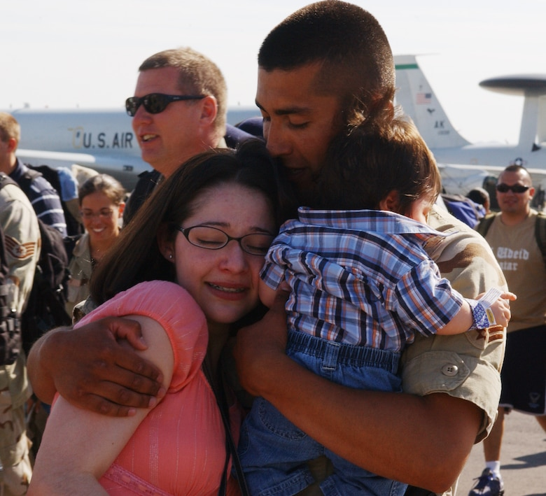 Senior Airmen Ruben Torres, 99th Civil Engineer Squadron firefighter, hugs his wife, Amanda, and their son upon returning to Nellis from deployment in Iraq May 13. About 50 Airmen returned after spending four months in support of Operation Iraqi Freedom. (U.S. Air Force Photo/Airman 1st Class Kasabyan Austin)
