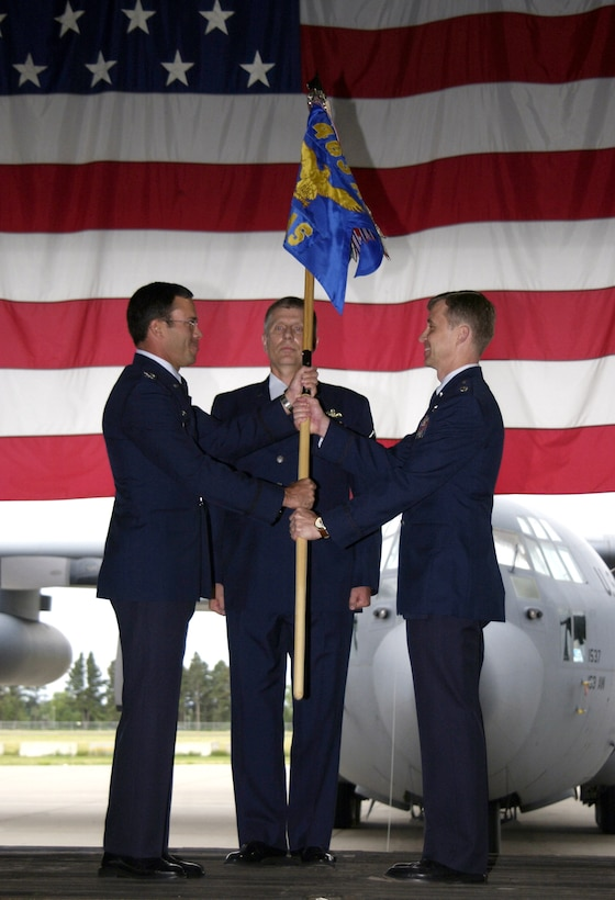 Col. John Gomez, left, passes the guidon to Lt. Col. Steven Hopkins while Master Sgt. Rick McKean observes during the 30th Airlift Squadron reactivation ceremony July 8 at the Wyoming Air National Guard base in Cheyenne.  The 30th AS is the first active duty air mobility squadron to report to an Air National Guard wing.  Colonel Gomez is the 463rd Airlift Group commander from Little Rock Air Force Base, Ark.  Sergeant McKean is also from the 463rd.  Colonel Hopkins is the 30th AS commander.  (U.S. Air Force photo/Tech. Sgt. Kimberly Spinner)