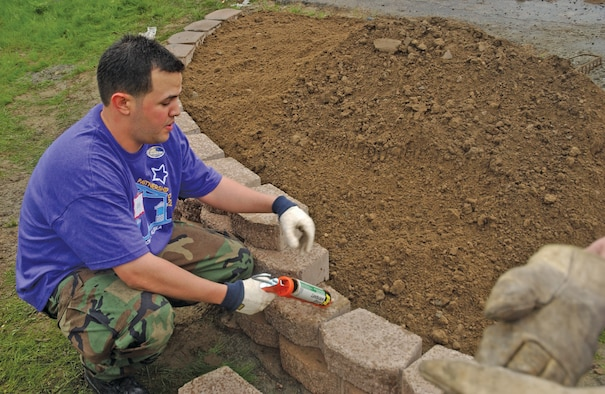 EIELSON AIR FORCE BASE, Alaska--Senior Airman Eddie Caro, 354th Fighter Wing command chief executive assistant, lays brick on one of seven planters constructed during Community Partnership Day. Military and civilian volunteers worked through day-long inclement weather to accomplish twice their projected goal. (U.S. Air Force photo by Airman Christopher Griffin)