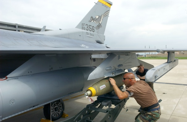 Tech. Sgt. Mike Geske, front, and Staff Sgt. Carl Valvota secure a Mark 82 bomb to an F-16 Fighting Falcon at Kunsan Air Base, South Korea, on July 5.  The aircraft is from the New Mexico Air National Guard's 150th Fighter Wing at Albuquerque.  (U.S. Air Force photo/Tech. Sgt. Erik Gudmundson)