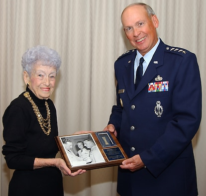 Mrs. Bea Erlenbusch, wife of the late Col. William Erlenbusch, presents the historic first missile badge Wednesday to General Lance W. Lord, Commander, Air Force Space Command . Colonel Erlenbusch earned the first U.S. Air Force guided missile insignia in 1958. (Photo by Joe Juarez)