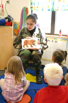 """Senior Airman Aremy Strickland, 50th Space Wing staff member, reads """"Brown Bear, Brown Bear, What Do You See?"""" in English and Spanish while the children read along with her. (Photo by Staff Sgt. Olenda Kleffner)"""