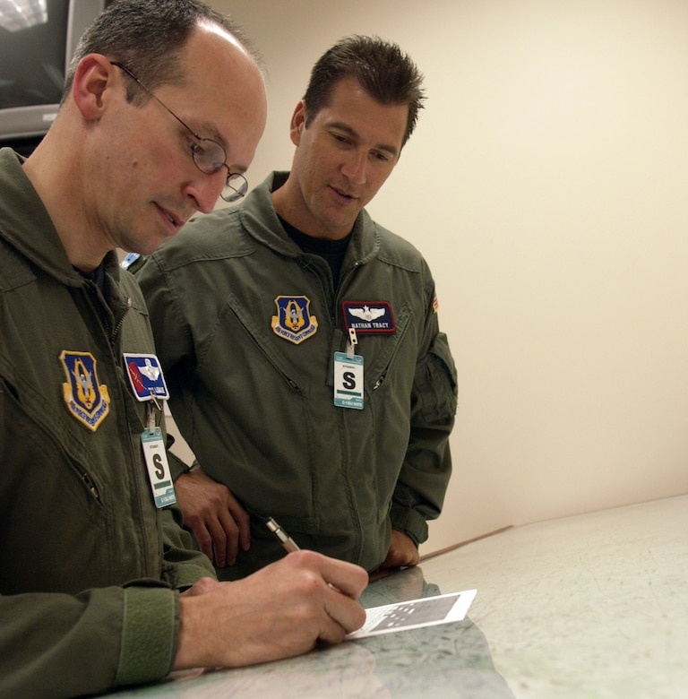 Maj. Nathan Tracy looks on as Maj. Pat Menaire, both C-130 aircrew students at Little Rock Air Force Base, Ark., points out a route during their flight planning training at the 714th Training Squadron.