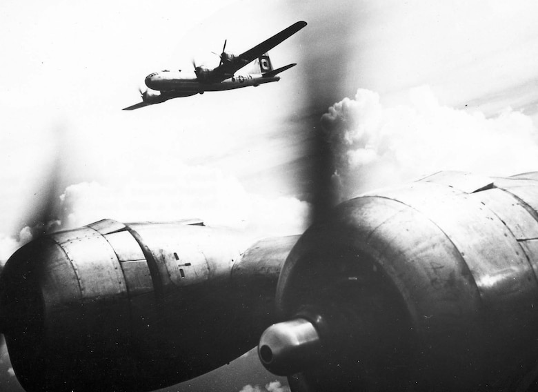 A B-29 with one engine out is escorted to Iwo Jima by another Superfortress. (U.S. Air Force photo)
