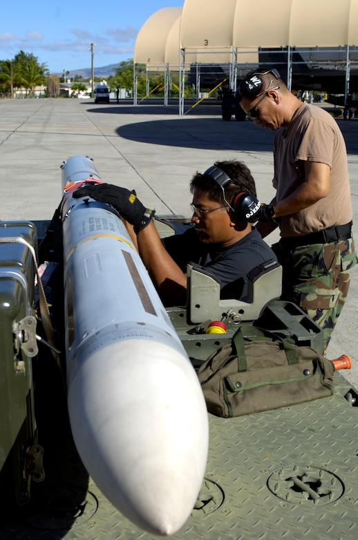 HICKAM AIR FORCE BASE, Hawaii -- Master Sgt. Baldwin Ojerio and Staff Sgt. Arthur Hamabata inspect an AIM-7 Sparrow missile before loading it on an F-15 Eagle at Hickam Air Force Base Hawaii July 16, 2006 during Rim of the Pacific Exercise 2006. The Airmen are from the Hawaii Air National Guard 154th Aircraft Maintenance Squadron. The Eagles will be firing 14 live missiles at two decoy targets during RIMPAC. RIMPAC 2006 brings friendly forces from the Pacific theater and the United Kingdom together to engage in air and sea war games. (U.S. Air Force photo/ Tech. Sgt. Shane A. Cuomo)