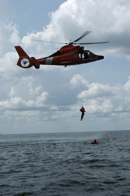 An aircrew member from the 317 AS gets picked up by a Coast Guard helicopter during aircrew survival training.  Pilots and loadmasters from the 315th Operations Group, Charleston AFB, S.C. participated in the one-day event that also included combat survival training. The group went through how to escape, evade and survive, what can be eaten in this situation, how the equipment can be used, and more survival tips. (Photo by Maj. Mark Johnson, USAFR)