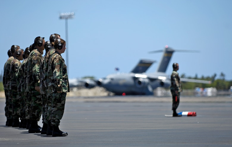 "Aircraft maintainers stand at attention while waiting for a C-17 Globemaster III to taxi to its parking spot at Hickam Air Force Base, Hawaii, on July 18.  The ""Spirit of Kamehameha- Imua"" is the eighth and final C-17 for the 15th Airlift Wing at Hickam. It marks the successful transformation for the 15th AW from a support unit to an operational strategic airlift wing. The maintainers are active duty Airmen and Hawaii Air National Guardsmen. (U.S. Air Force photo/Tech. Sgt. Shane A. Cuomo)"