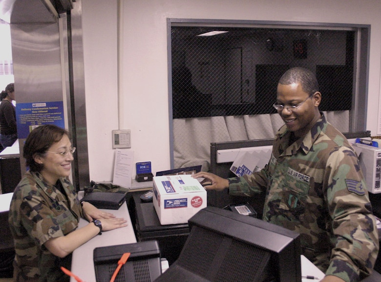 MISAWA AIR BASE, Japan -- A customer at the post office here, Maj. Regina Agee (left), is helped at the service counter by Staff Sgt. Jason Williams, 35th Communications Squadron finance postal clerk, who ensures that all packages are properly addressed and weighed. Friendly customer service contributed to Misawa winning the award for the best large postal facility in the Air Force.  (Air Force photo coutesy of 35th Fighter Wing Public Affairs)