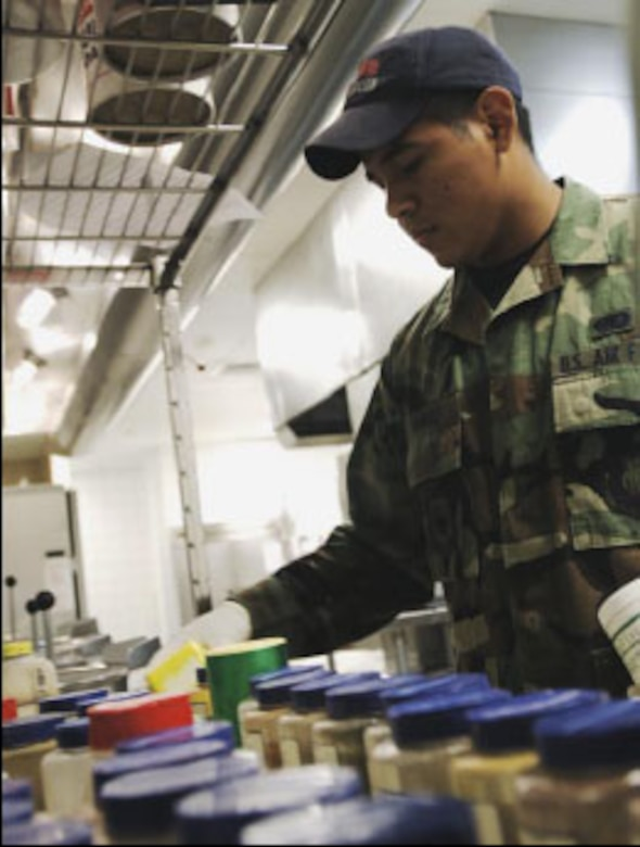 Airman Jesus Ramirez, 22nd Services Squadron chef, gathers ingredients from the spice rack to prepare cornmeal dressing for one of the lunch meals. (U.S. Air Force photo/Master Sgt. Maurice Hessel)