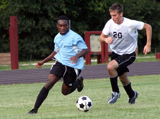 The 16th Component Maintenance Squadron's Richard Bonsra, left, sprints past the 16th Logistics Readiness Squadron's Brandon Bertoszek during the second half of the intramural soccer match July 18.  CMS beat LRS 2-1 fueled by two first-half goals.  (Air Force photo by Master Sgt. Stuart Camp)