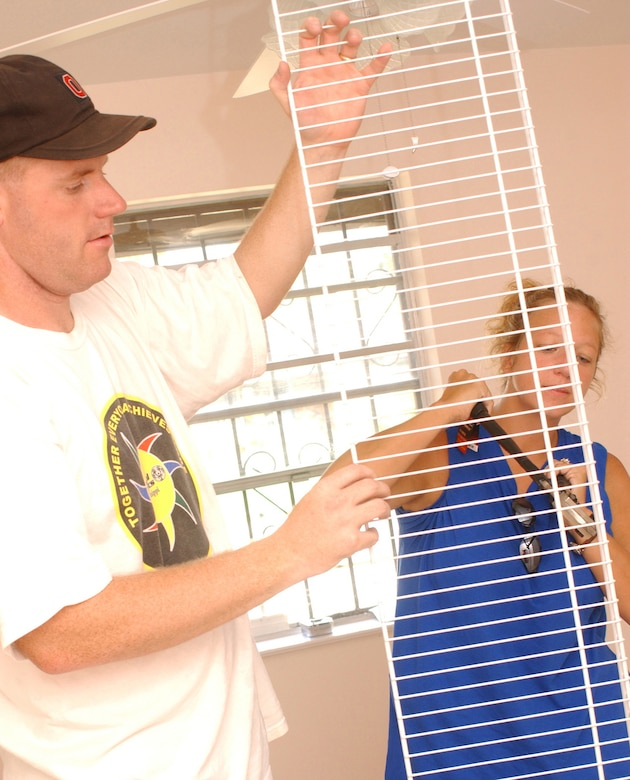 KEESLER AIR FORCE BASE, Miss. (AETCNS) -- Keesler NCO Academy classmates Tech. Sgts. Steven Baldinger, left, and Tammy Down prepare a wire shelf for a closet at a Biloxi home July 14. The class adopted the Hurricane Katrina-damaged home as a community service project. Sergeant Baldinger is from the 26th Operational Weather Squadron at Barksdale Air Force Base, La., and Sergeant Down is assigned to the 81st Medical Support Squadron at Keesler. (Photo by Kemberly Groue)