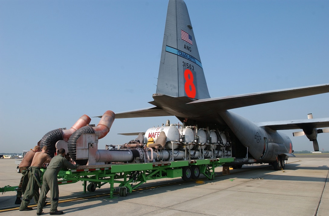 Airmen from the North Carolina Air National Guard's 145th Airlift Wing push a modular airborne fire fighting system onto a C-130 Hercules. The pressurized tanks hold 3,000 gallons of flame-retardant liquid. The retardant is dropped along the leading edge of a fire to block the spread of flames. (U.S. Air National Guard photo/Tech. Sgt. Brian E. Christiansen)