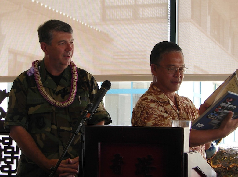"HICKAM AIR FORCE BASE, Hawaii -- General Paul V. Hester, commander, Pacific Air Forces receives a commemorative book from Don Ho, Chinese Chamber of Commerce.  The book details the history of the famed ""Flying Tigers"" and 14th Air Force under the command of Maj. Gen. Claire Chennault and is signed by a Chinese ground crew member living in China.  The General spoke to the Chinese Chamber of Commerce of Hawaii Thursday regarding the importance of diplomatic relationships in the Pacific and with China in particular.  (Air Force photo by Capt Allison Farabaugh)"