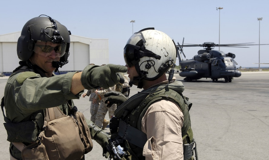Maj. Jason Stanley, left, talks with a Marine crew member waiting to take Secretary of State Condoleezza Rice from Cyprus to the U.S. Embassy in Beirut, Lebanon, July 24.  Major Stanley, an MH-53M Pave Low helicopter pilot with the 352nd Special Operations Group, Royal Air Force Mildenhall, was providing escort to the Marine helicopter transporting Secretary Rice.   (U.S. Air Force photo/Senior Airman Brian Ferguson)