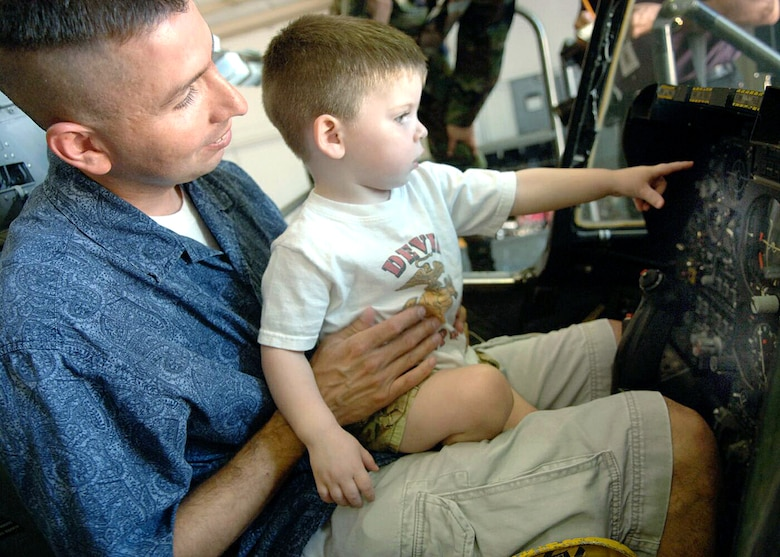 Mark Holguin holds his son, Jacob, 2, as they sit in the cockpit of an A-10 Thunderbolt II during a tour of Davis-Monthan Air Force Base, Ariz., on July 17. The Make-A-Wish Foundation teamed with Davis-Monthan to offer a tour of the base for Jacob and other Make-A-Wish children as well as their families. The tour consisted of demonstrations by an explosive ordnance disposal robot, base fire department and a weapons load crew for an A-10. (U.S. Air Force photo/Senior Airman Christina D. Ponte)