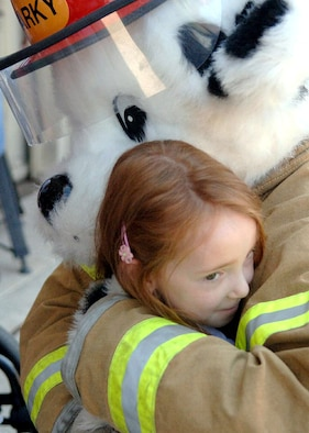 Hannah Mockbee hugs Sparky the fire safety dog during a tour of Davis-Monthan Air Force Base, Ariz., on July 17. The Make-A-Wish Foundation teamed with Davis-Monthan to offer a tour of the base for Hannah and other Make-A-Wish children as well as their families. The tour consisted of demonstrations by an explosive ordnance disposal robot, base fire department and a weapons load crew for an A-10 Thunderbolt II. Hannah is the daughter of Jeff and Stacie Mockbee. (U.S. Air Force photo/Senior Airman Christina D. Ponte)