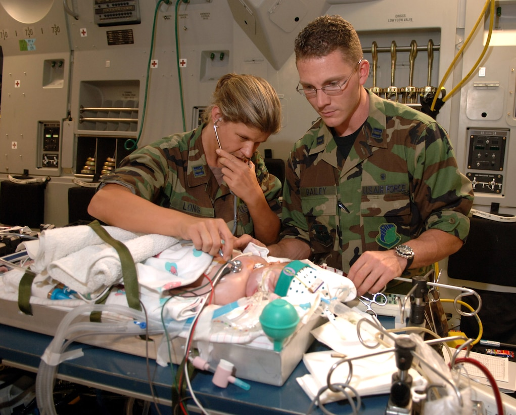 Capts. Karen Long and James Bailey monitor the vital signs and blood flow of 3-day-old Stuart Parker aboard a C-17 Globemaster III on July 21. An Extracorporeal Membrane Oxygenation team comprised Air Force and Army medical specialists from the Wilford Hall Medical Center at Lackland Air Force Base, Texas, flew to San Juan, Puerto Rico, to transport Stuart to San Antonio for more advanced care. Captain Long is a neonatal intensive care nurse and Captain Bailey is a pediatric intensive care nurse assigned to the Wilford Hall Medical Center. (U.S. Air Force photo/Master Sgt. Scott Reed)
