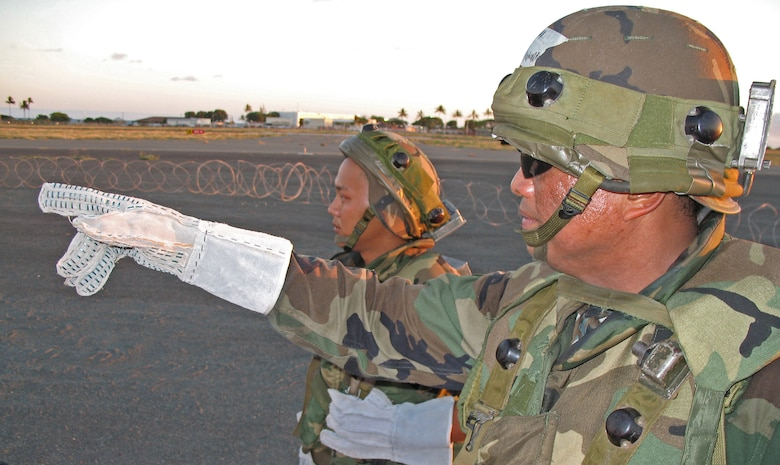 BARBER?S POINT, Hawaii -- Master Sgt. Rodney Arguilles points out holes in the razor wire fence as he and Senior Airman Pat Takenishi discuss base defense strategies during an exercise at Barber's Point, Hawaii, on 25 July, 2006.  Both Airmen are with the Hawaii Air National Guard's 297th Air Traffic Control Squadron.  (US Air Force photo by Tech. Sgt. Chris Vadnais)