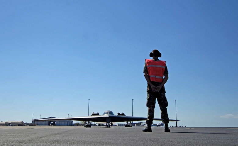 Staff Sgt. Jeremy Hord waits to marshal a B-2 Spirit stealth bomber from its parking spot at Royal Australian Air Force Base Darwin on July 27 during exercise Green Lightning. The exercise tests U.S. capabilities and provides operational familiarity in the region for the Pacific bomber presence while also serving to enhance relations with the Australians. Sergeant Hord is from the 509th Aircraft Maintenance Squadron at Whiteman Air Force Base, Mo.  (U.S. Air Force photo/Tech. Sgt. Shane A. Cuomo)