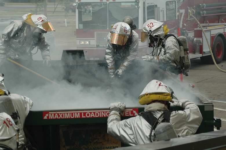 MINOT AIR FORCE BASE, N.D. -- Airmen from the 5th Civil Engineer Squadron fire protection flight, extinguish a fire in a trash dumpster in front of the PRIDE building here July 21. Airmen responded to the fire within one minute after receiving the 911 call. (U.S. Air Force photo by Capt. James Breessendorf.)