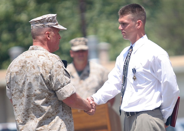 Lt. Gen. John F. Sattler, commanding general of the I Marine Expeditionary Force, congratulates former Marine Sgt. Robert J. Mitchell on his receipt of the Navy Cross during a ceremony aboard Camp Pendleton, Calif., July 28, 2006.  Mitchell, who was wounded four times during his two tours in Iraq, received the medal, the nation's second-highest award for battlefield heroism, in recognition of his actions during the battle for Fallujah, Iraq in November 2004.