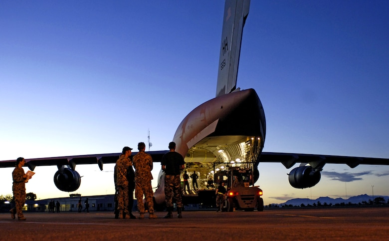 Airmen from the Australian 1st Air Terminal Squadron observe the loading of equipment onto a C-17 Globemaster III at Honiara International Airport, Solomon Islands, on Sunday, May 28, 2006. Two C-17s from the 15th Airlift Wing and Hawaii Air National Guard's 154th Wing at Hickam Air Force Base, Hawaii, are helping the Australian Defense Force reposition its forces to better support peace operations in East Timor. (U.S. Air Force photo/Tech. Sgt. Shane A. Cuomo)