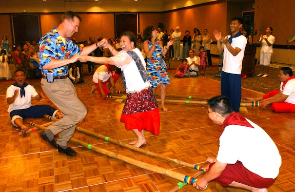 """Col. Steve Arquiette, 60th Air Mobility Wing commander, performs the Tinikling, the Philippines' national dance, with Carrie Basaca, Travis Youth Center school age coordinator, during the Asian Pacific American Heritage Banquet May 30. The Tinikling is a fast rhythmic dance that mimics the movements of the """"tikling"""" birds in the rice fields in their effort to avoid being clipped with the bamboo traps. (U.S. Air Force photo by Nan Wylie)"""