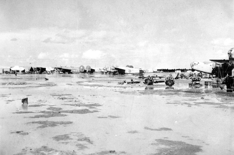 "58th Service Squadron depot. Note the standing water and the engines laying on the ground. The Consolidated B-24D ""Strawberry Bitch"" is in the center of the photo (with vertical stabilizers removed). (U.S. Air Force photo)"