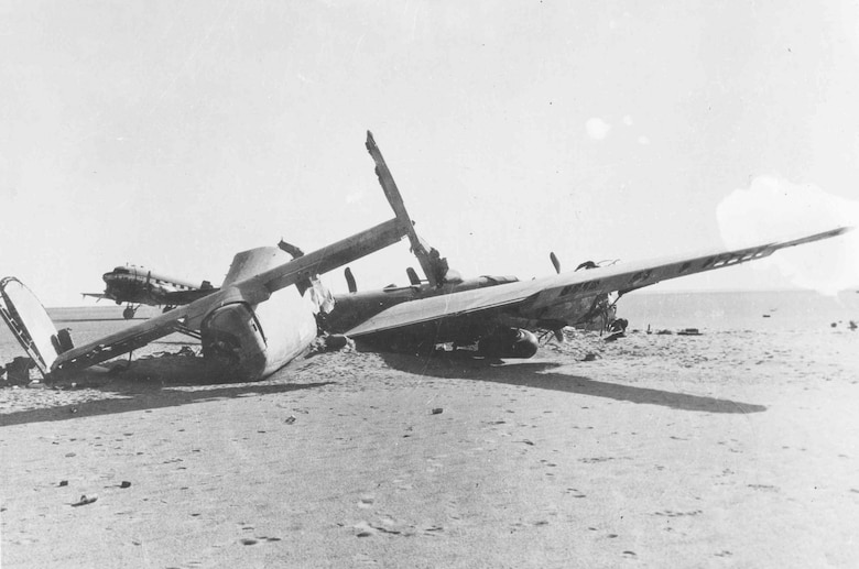 "Tail view of the crashed Consolidated B-24D ""Lady Be Good."" Note the C-47 recovery aircraft parked in the background. (U.S. Air Force photo)"