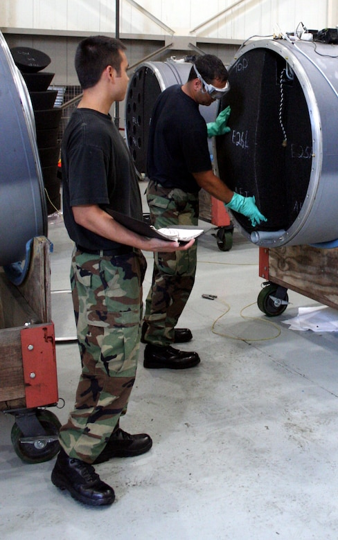 (Left) Airmen 1st Class Jeremy Macomber and Senior Airman Matthew Mendiola, 16th Component Maintenance Squadron, inspect a fuel tank from one of the AC-130U Gunship as part of the operational readiness inspection.