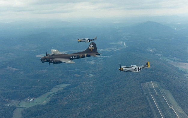 """Boeing B-17G """"Shoo Shoo Shoo Baby"""" with P-51 escort during its flight to the National Museum of the United States Air Force on Oct. 12, 1988. (U.S. Air Force photo)"""