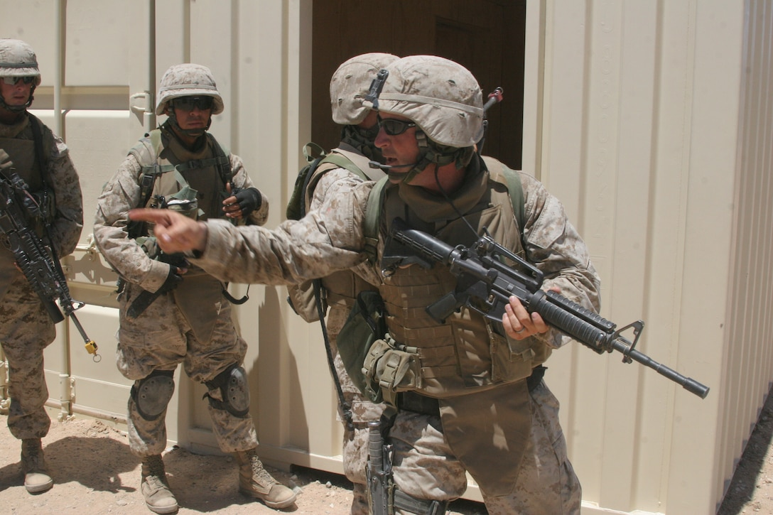 Sgt. Joshua C. Hudson, a squad leader with 1st Squad, 3rd Platoon, Bravo Company, 1st Battalion, 6th Marine Regiment, directs members from his squad toward certain areas aboard Combat Center Range 215 June 5.
