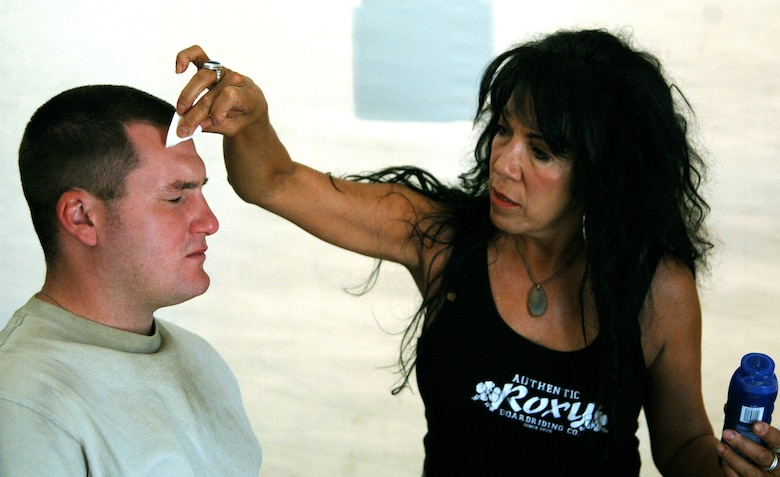 """Makeup artist Linda Vallejo applies makeup and sunscreen to Airman 1st Class Joshua Clanton on the set of the movie """"Transformers"""" at Holloman Air Force Base, N.M., on Tuesday, May 30, 2006. The movie is scheduled for release in June 2007. Airman Clanton is with the 49th Mission Support Squadron at Holloman AFB. (U.S. Air Force photo/Tech. Sgt. Larry A. Simmons)"""
